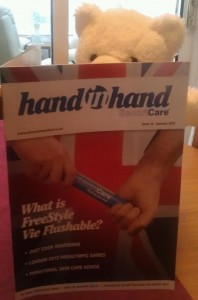 Fuzzbutt reads the latest edition of SecuriCare's Hand in Hand magazine.